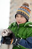 The boy holds a polecat Royalty Free Stock Photo