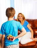 Boy holds present behind to surprise  mother Royalty Free Stock Photo