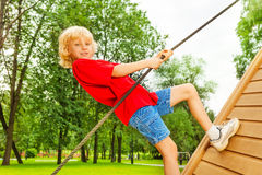 Boy holds rope and climbs on wooden construction. Of playground in summer Royalty Free Stock Photo
