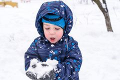 The boy holds snow in hands. active winter time outdoors royalty free stock photos