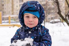 The boy holds snow in hands. active winter time outdoors royalty free stock photo
