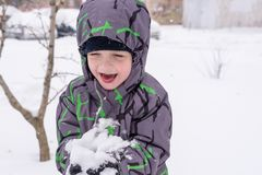 The boy holds snow in hands Stock Photo