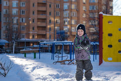 The boy holds snow in hands. Happy kid walking outdoors in winter city. Child smiling and having fun. Royalty Free Stock Photos