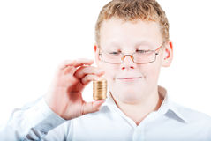 Boy holds a stack of coins. On white background Royalty Free Stock Photography
