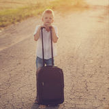 The boy holds a suitcase in a summer sunny day Royalty Free Stock Photos