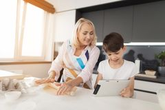 The boy holds a tablet in his hands and shows his grandmother a cookie recipe. Grandmother rolls out the dough. The boy holds a tablet in his hands and shows his Stock Image