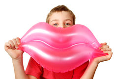 Boy holds toy, inflatable pink lips. Royalty Free Stock Photos