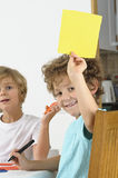 Boy holds up blank yellow card Royalty Free Stock Image