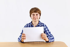 A boy holds up a sheet of paper Stock Photo