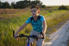 Young boy with injuries riding a bike stock photo