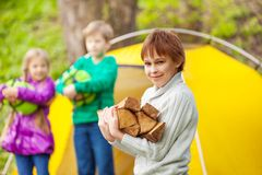 Boy holds the wood for bonfire during camping Stock Photography