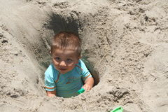 Boy In a Hole. Boy sitting in a deep hole at the beach Royalty Free Stock Image