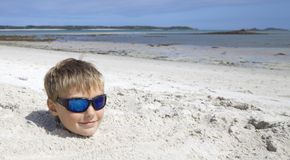Boy on holiday buried in the sand Royalty Free Stock Images