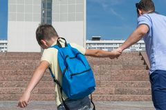 The boy after the holidays does not want to study and go to school, resists his parents royalty free stock image
