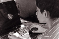 Boy and home computer. Boy playing at home computer, looking to the monitor Royalty Free Stock Images