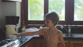 Boy in home kitchen holds a glass of water Stock Photos
