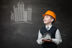 Boy with home model looks at drawing of buildings. Portrait of boy in hard hat keeping home model and looking at chalky drawing of buildings on grey background Stock Photography
