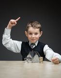 Boy with home model and pile of coins Royalty Free Stock Photos