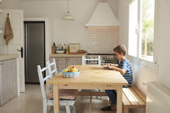 Boy At Home Using Laptop On Kitchen Table Royalty Free Stock Images