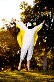 Boy In Homemade Bat Costume. A young boy in a homemade bat costume jumps in the air, arms up and spread wide. He is in a park with late afternoon sunlight behind Royalty Free Stock Photography