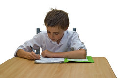 Boy with homework. An isolated image of a teenage boy doing his school work / homework sat at a table stock photos