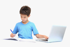 A boy with homework. A boy doing his homework with a laptop,notebook and pen isolated on a white background royalty free stock photos
