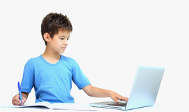 A boy and homework. A boy making his homework using a laptop,a notebook and a pen isolated on a white background royalty free stock image