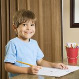 Boy with homework. Hispanic boy smiling at viewer and doing homework Royalty Free Stock Images