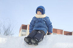 Boy In Hooded Jacket Sitting On Snow Heap Royalty Free Stock Image
