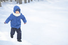 Boy In Hooded Jacket Walking In Snow Royalty Free Stock Photos