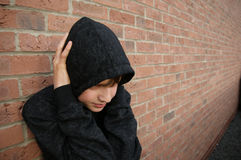 Boy in hooded top. With brickwall background Royalty Free Stock Photography