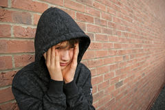 Boy in hooded top. With brickwall background Royalty Free Stock Photos