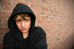 Boy in hooded top. With brickwall background Royalty Free Stock Image