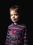 Boy with hoodie standing over black background Stock Images