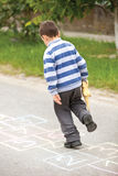 Boy on the hopscotch Stock Images