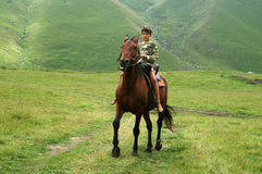 The boy on the horse. Caucasus, summer Stock Images