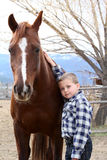 Boy and Horse. Young boy in blue leaning against his horse Stock Photography