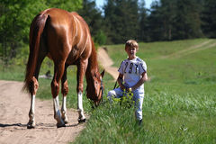 Boy with a horse on a break during horse race. SAINT-PETERSBURG, RUSSIA - MAY 30, 2009 Stock Photos