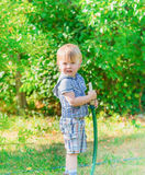 Boy with hose Stock Images