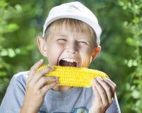 Boy and hot corn Royalty Free Stock Image