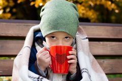 Boy with hot mug of tea. A little boy with a hot mug of tea, wrapped in a warm blanket, on an outdoor bench in autumn Stock Photos