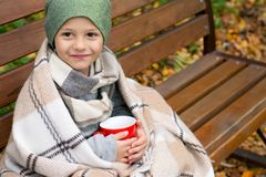 Boy with hot mug of tea. A little boy with a hot mug of tea, wrapped in a warm blanket, on an outdoor bench in autumn Stock Photography