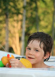 Boy in Hot Tub. A young boy squirting water from a toy while enjoying a soak in a Hot Tub stock photo