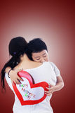 Boy hug mother holding love card. On red Stock Photo