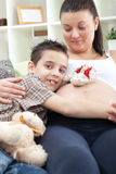 Boy hugging belly of pregnant mother on sofa Royalty Free Stock Photo