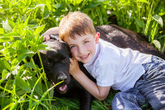 Boy hugging a big dog in an outdoor setting royalty free stock photo