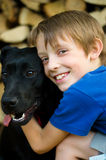 Boy hugging black dog Royalty Free Stock Photo