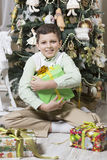 Boy is hugging Christmas gifts Royalty Free Stock Photos