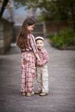 Boy hugging cute sister and looks up Royalty Free Stock Photography
