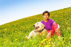 Boy hugging dog sitting on green grass in summer Royalty Free Stock Images